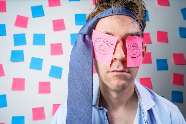 Homme avec des post-its sur les yeux