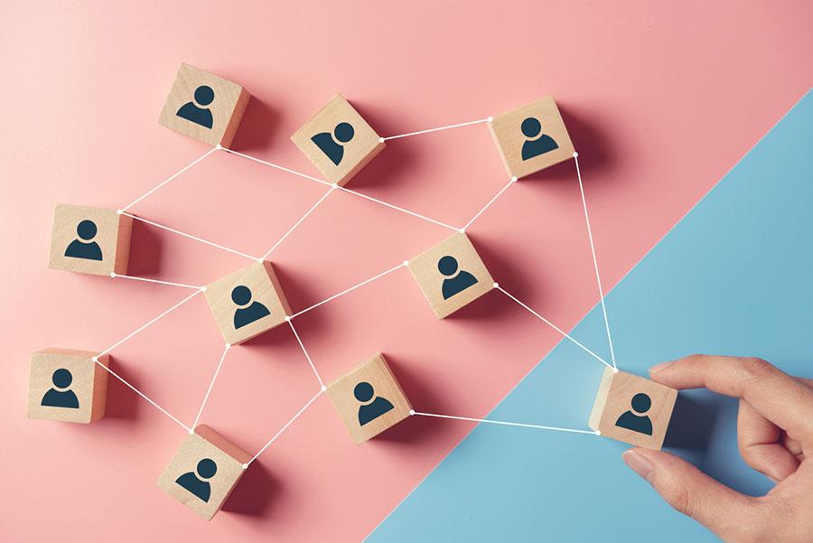 Main manipulant des cubes constituant un réseau de personnes